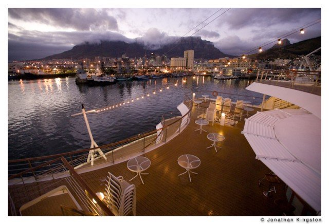 A night view from the stern of a cruise ship, looking towards the harbor and the Victoria and Alfred Waterfront of Cape Town, South Africa. (Photo by Jonathan Kingston/Aurora)